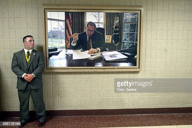 A secret service agent stands next to a photograph of President George W Bush at the Republican National Convention in New York City