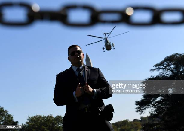 Secret service agent stands still as US President Joe Biden aboard Marine One departs the South Lawn of the White House in Washington, DC, on October...
