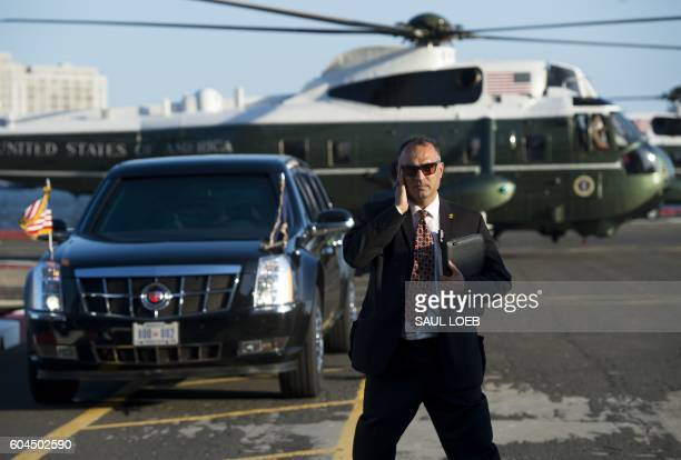 Secret Service Agent stands watch as Marine One with US President Barack Obama aboard lands alongside the Presidential limousine at the Downtown...