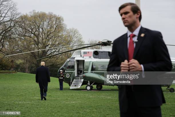 S Secret Service agent stands watch as President Donald Trump walks across the South Lawn before boarding Marine One at the White House April 05 2019...
