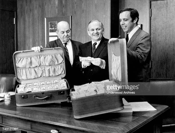 A Secret Service agent the US Attorney and the District Attorney show off two suitcases of captured counterfeit money New York New York May 8 1972
