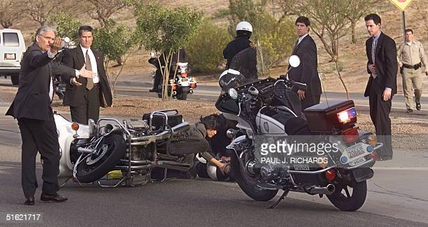 Secret Service agents and Tucson police officers secure the accident scene as one of US President Bill Clinton's traveling physicians gives emergency...