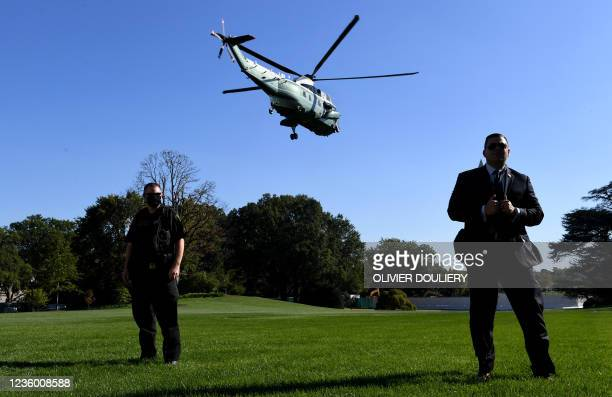 Secret service agents stand still as US President Joe Biden aboard Marine One departs the South Lawn of the White House in Washington, DC, on October...
