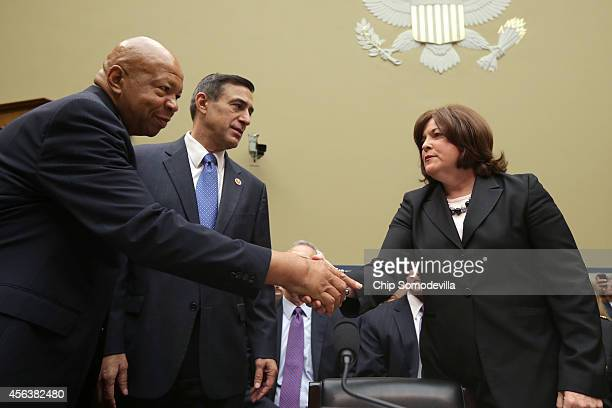 Secret Service Director Julia Pierson greets chairman of the House Oversight Committee US Rep Darrel Issa and Rep Elijah Cummings before she...