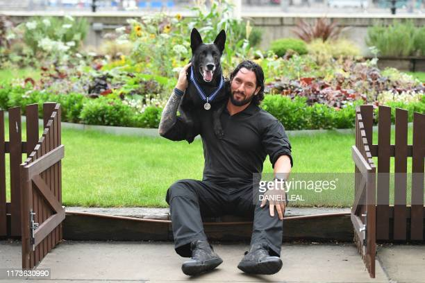 US Secret Service dog Hurricane and his handler Officer Marshall Mirarchi pose after Hurricane received the PDSA Order of Merit from UK veterinary...