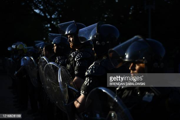 Secret Service in riot gear stand guard while US President Donald Trump visits St John's Episcopal church across Lafayette Park in Washington DC on...