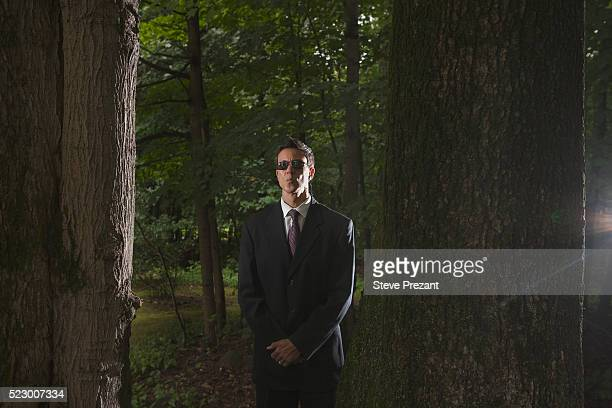 Secret service man standing in a forest