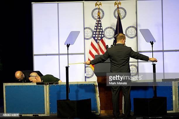 Secret service members erect a security barrier on stage while another holds up a white balance poster at the 106th NAACP national convention on July...