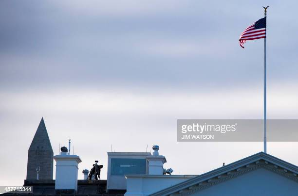 Secret Service officer sets up a binocular watch post atop the White House in Washington DC October 23 2014 A suspect who climbed over the White...