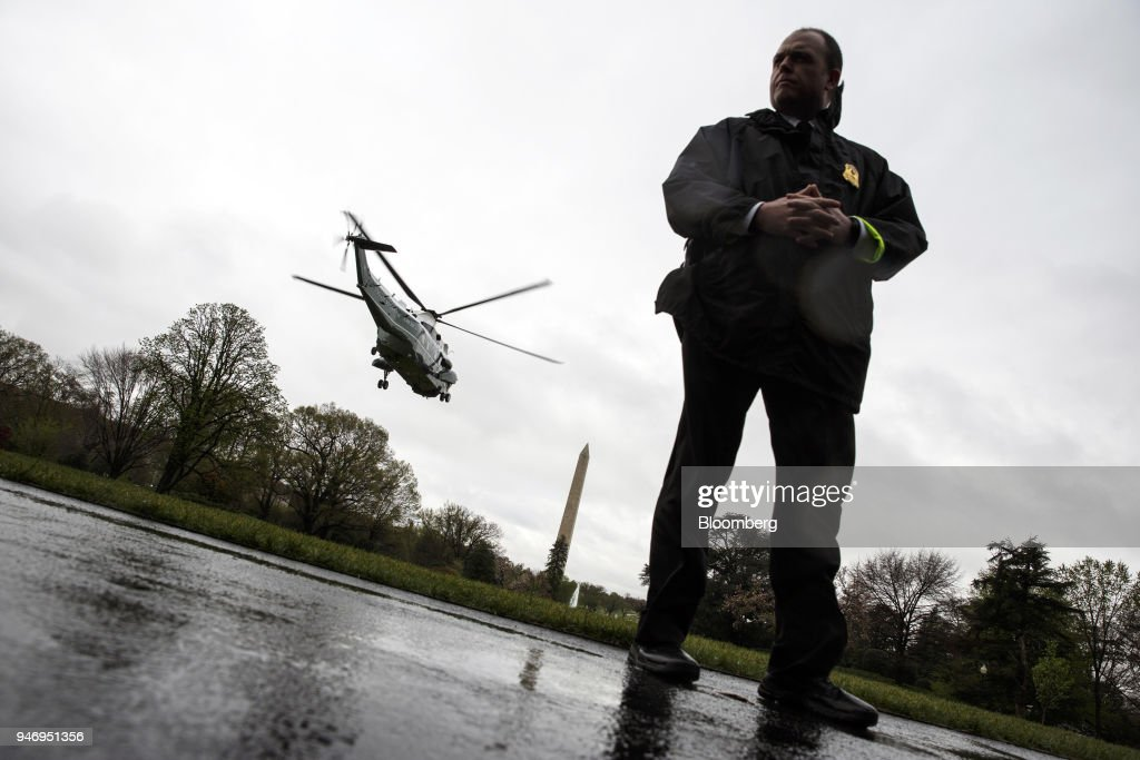 A Secret Service officer stands by as Marine One, with U.S. President Donald Trump on board, departs for Miami from the South Lawn of the White House in Washington, D.C., U.S. on Monday, April 16, 2018. Trumpaccused China and Russia of devaluing their currencies, opening a new front in his argument that foreign governments are taking advantage of the U.S. economy to support their own expansions. Photographer: Joshua Roberts/Bloomberg via Getty Images
