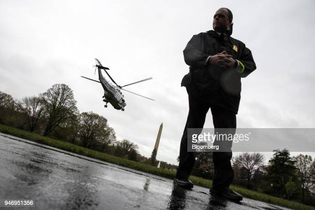 A Secret Service officer stands by as Marine One with US President Donald Trump on board departs for Miami from the South Lawn of the White House in...