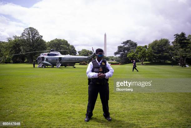 A secret service officer stands guard as US President Donald Trump left walks towards Marine One to depart for Cincinnati on the South Lawn of the...