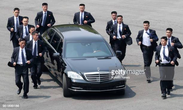 Secret service personnel run beside a vehicle carrying North Korean leader Kim Jong Un after a meeting with South Korean President Moon Jae In in...