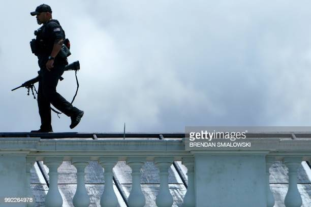 A Secret Service sniper walks on top of the North Portico of the White House on July 5 2018 in Washington DC