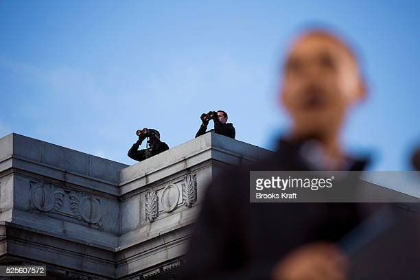 Secret Service snipers watch on a rooftop as President Barack Obama speaks at a campaign rally in Concord NH