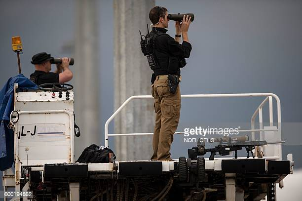 US Secret Service use binoculars to scan the surroundings as they wait for US President Barack Obama to board Air Force One following the closing...