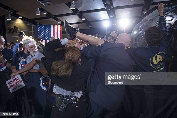 Secret service wrestle with a protester as Hillary Clinton 2016 Democratic presidential nominee not pictured speaks during a campaign event in Las...