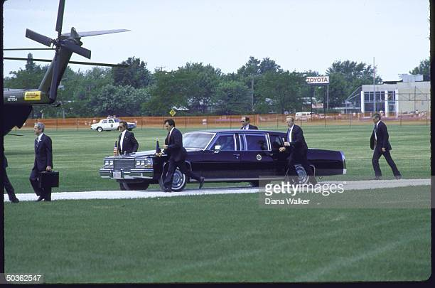 Secret servicemen escort President Reagan's Limo, as NSC Advisor Robert McFarlane, walks by.