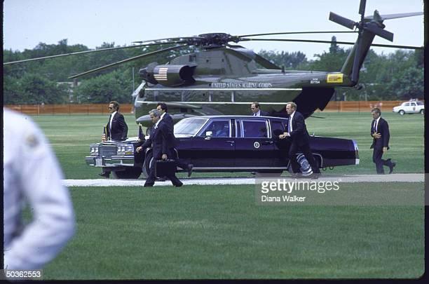 Secret servicemen escort President Reagan's Limo as NSC Advisor Robert McFarlane walks by