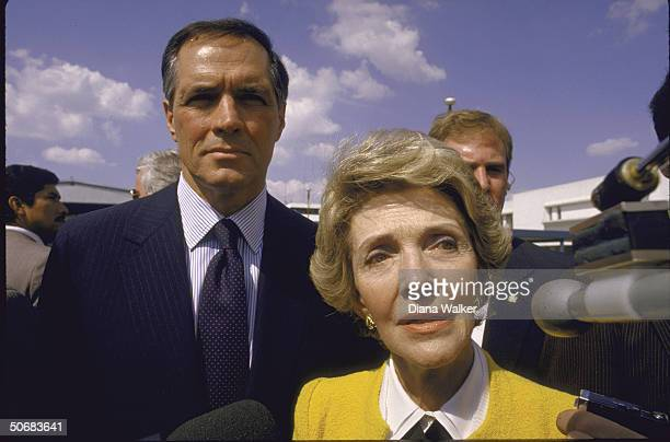 Secret servicemen stand near wife of US Pres Mrs Ronald W Reagan who is speaking to the press while in country with US Amb to Mexico John Gavin...