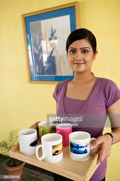 Secretary carrying a tray of mugs