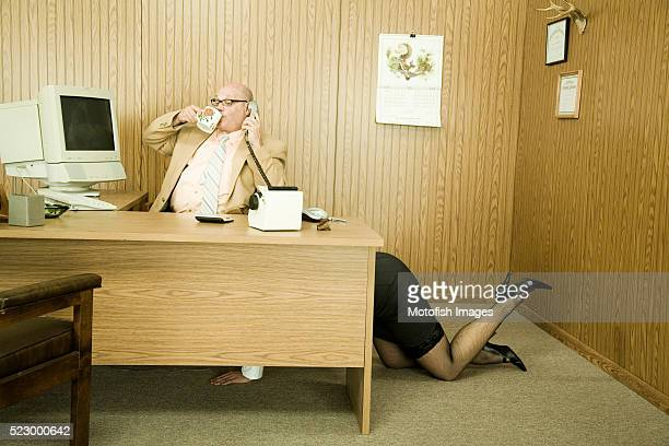 Secretary Crawling Under Businessman's Desk