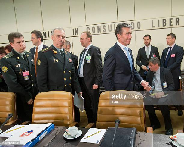 NATO Secretary General Anders Fogh Rasmussen and acting Ukrainian Defense Minister Mikhail Koval take their seats during a meeting at NATO...