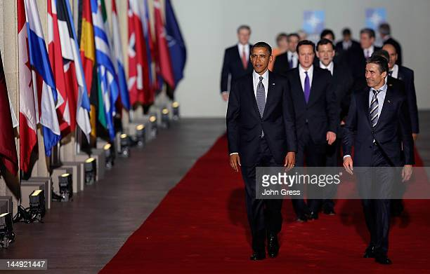 Secretary General Anders Fogh Rasmussen , U.S. President Barack Obama , and other world leaders arrive for a group photo at the NATO summit on May...