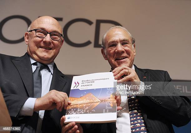 Secretary General Angel Gurria and French Finance Minister Michel Sapin address a press conference for the launching of the OECD economic survey of...