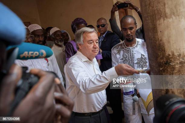UN Secretary General Antonio Guterres applies paint on a pillar as he meets with the local committee for peace and reconciliation in the 3rd district...