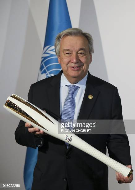 Secretary General Antonio Guterres holds an Olympic torch during a statement to the press with the International Olympic Committee President ahead of...