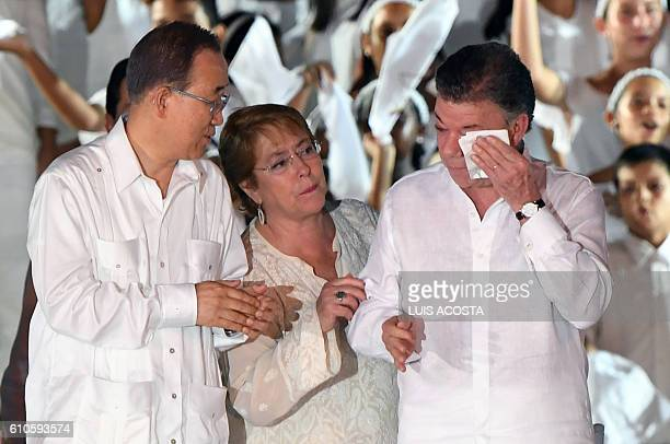 Secretary general Ban Kimoon and Chilean President Michelle Bachelet look at Colombian President Juan Manuel Santos at the end of the signing...
