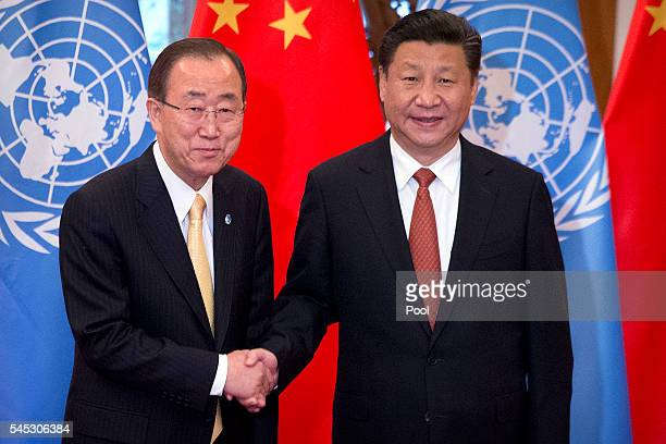 Secretary General Ban Ki-moon, left, and Chinese President Xi Jinping, right, shake hands as they pose for a photo at the Diaoyutai State Guesthouse...
