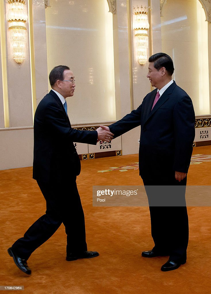 UN Secretary General Ban Ki-moon, (L) shakes hand with Chinese President Xi Jinping as they pose for photographers during a meeting at the Great Hall of the People on June 19, 2013 in Beijing, China.