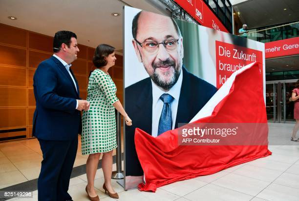 SPD Secretary general Hubertus Heil and SPD managing director Juliane Seifert unveil one of their party's electoral posters featuring SPD chairman...