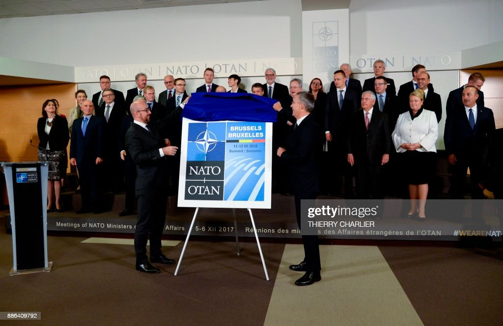 Secretary General Jens Stoltenberg (R) and Belgian Prime Minister Charles Michel (L) unveil the Brussels 2018 NATO Summit Logo during a NATO Foreign Affairs Ministers' meeting held at NATO headquarter in Brussels, on December 5, 2017. /