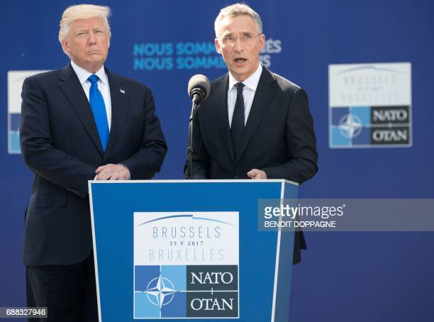 Secretary General Jens Stoltenberg flanked by US President Donald Trump speaks during the unveiling ceremony of the new headquarters of NATO on May...