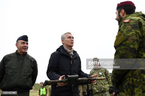 Secretary General Jens Stoltenberg holds a Tac 50 Mac Millan sniper riffle as he meets with members of the Canadian Army Patrol Pathfinder taking...