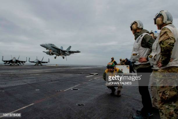 Secretary General Jens Stoltenberg looks at a F18 Super Hornet landing on of the US Nimitzclass aircraft carrier USS Harry S Truman in The North Sea...