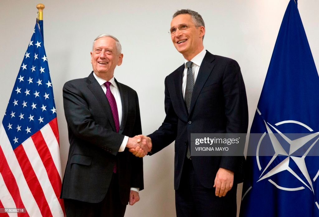 Secretary General Jens Stoltenberg (R) shakes hands with US Secretary for Defense James Mattis prior to a meeting of the North Atlantic Council (NAC) at the NATO headquarters in Brussels on February 14, 2018. / AFP PHOTO / POOL / Virginia Mayo