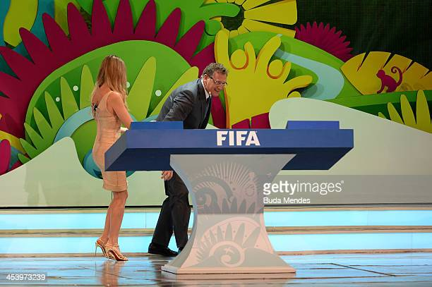 Secretary General Jerome Valcke collects one of the draw balls after was dropped on the floor next to host Fernanda Lima during the Final Draw for...