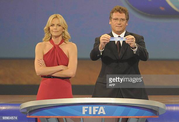 Secretary general Jerome Valcke flanked by South African actress Charlize Theron as he holds up Australia during the World Cup 2010 draw at the Cape...