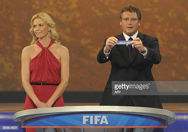 Secretary general Jerome Valcke flanked by South African actress Charlize Theron as he holds up New Zealand during the World Cup 2010 draw at the...