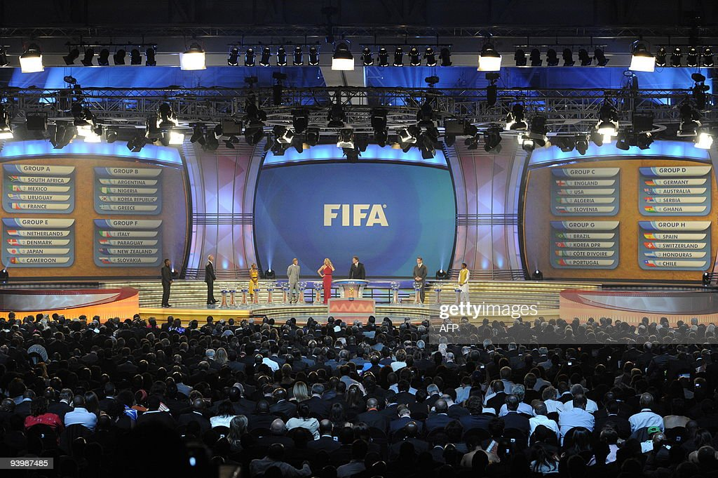 FIFA secretary general Jerome Valcke (C-R) flanked by South African actress Charlize Theron stand with the full 8 groups on the big screens after the World Cup 2010 draw at the Cape Town International Convention Centre (CTICC) in Cape Town on December 4, 2009. The draw itself sees the 32 teams divided into four pots of eight from which the eight groups that will contest the first round will be drawn.