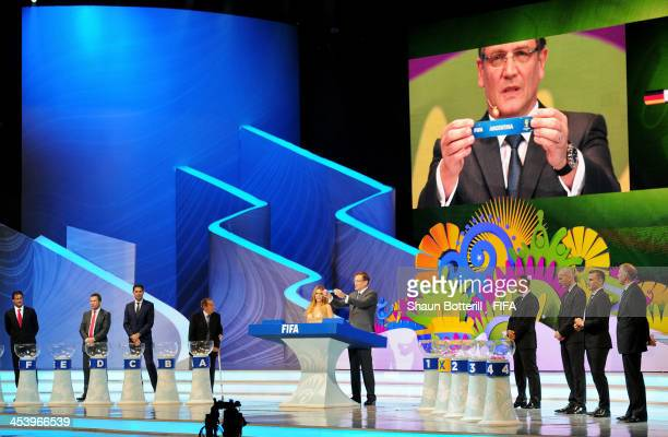Secretary General Jerome Valcke holds up the name of Argentina during the Final Draw for the 2014 FIFA World Cup Brazil at Costa do Sauipe Resort on...