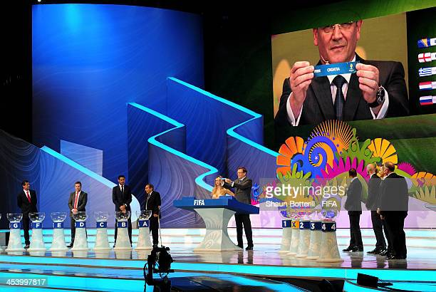 Secretary General Jerome Valcke holds up the name of Colombia during the Final Draw for the 2014 FIFA World Cup Brazil at Costa do Sauipe Resort on...