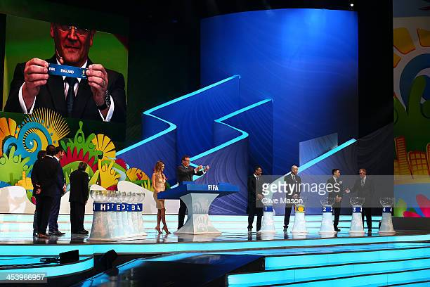 Secretary General Jerome Valcke holds up the name of England during the Final Draw for the 2014 FIFA World Cup Brazil at Costa do Sauipe Resort on...