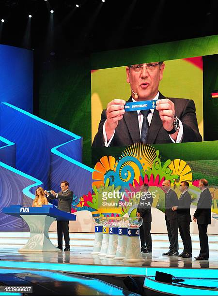 Secretary General Jerome Valcke holds up the name of Switzerland during the Final Draw for the 2014 FIFA World Cup Brazil at Costa do Sauipe Resort...