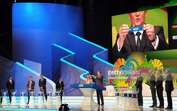Secretary General Jerome Valcke holds up the name of Uruguay during the Final Draw for the 2014 FIFA World Cup Brazil at Costa do Sauipe Resort on...