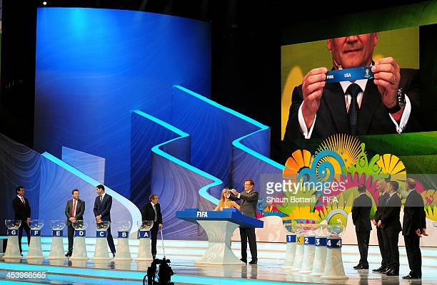 Secretary General Jerome Valcke holds up the name of USA during the Final Draw for the 2014 FIFA World Cup Brazil at Costa do Sauipe Resort on...